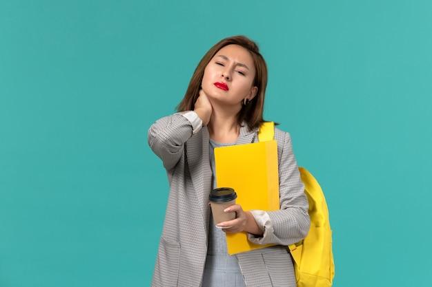 Vista frontal da aluna em uma jaqueta cinza com sua mochila amarela segurando arquivos e café na parede azul