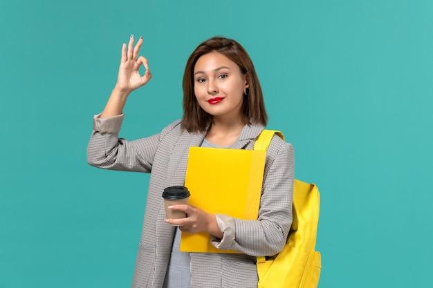 Vista frontal da aluna em uma jaqueta cinza com sua mochila amarela segurando arquivos e café sorrindo na parede azul-clara