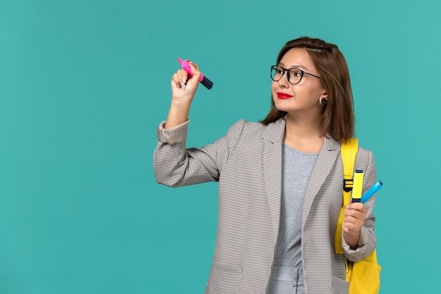 Vista frontal da aluna em uma jaqueta cinza com sua mochila amarela segurando canetas de feltro na parede azul clara