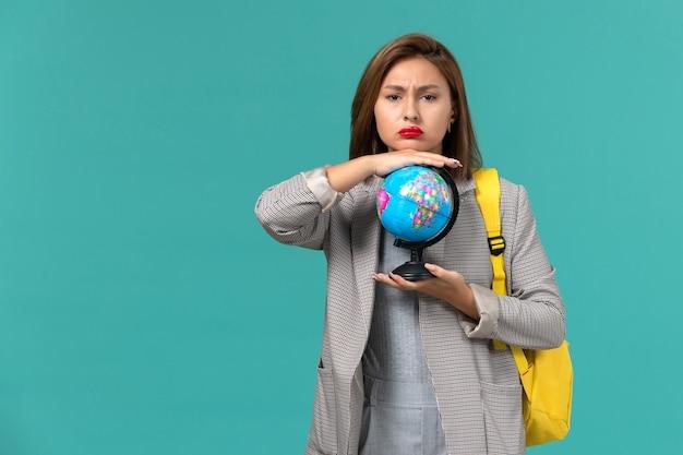 Vista frontal da aluna em uma jaqueta cinza com sua mochila amarela segurando o globo na parede azul clara