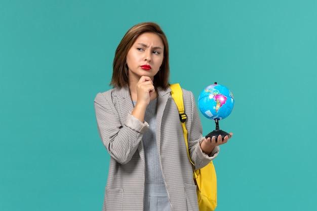 Vista frontal da aluna em uma jaqueta cinza com sua mochila amarela segurando o pequeno globo pensando na parede azul claro