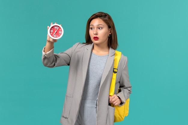 Vista frontal da aluna em uma jaqueta cinza com sua mochila amarela segurando relógios na parede azul