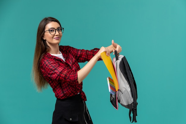 Vista frontal da aluna segurando mochila e arquivos na parede azul clara