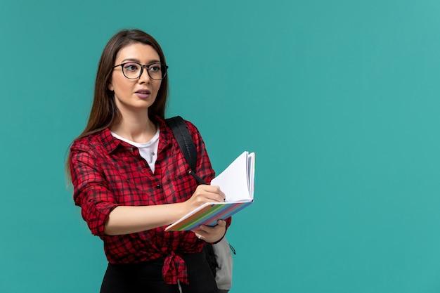Vista frontal da aluna segurando o caderno e uma caneta escrevendo na parede azul clara