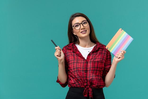 Vista frontal da aluna segurando o caderno e uma caneta na parede azul clara