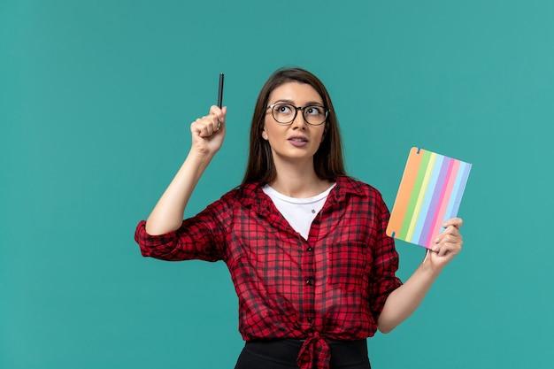 Vista frontal da aluna segurando o caderno e uma caneta na parede azul