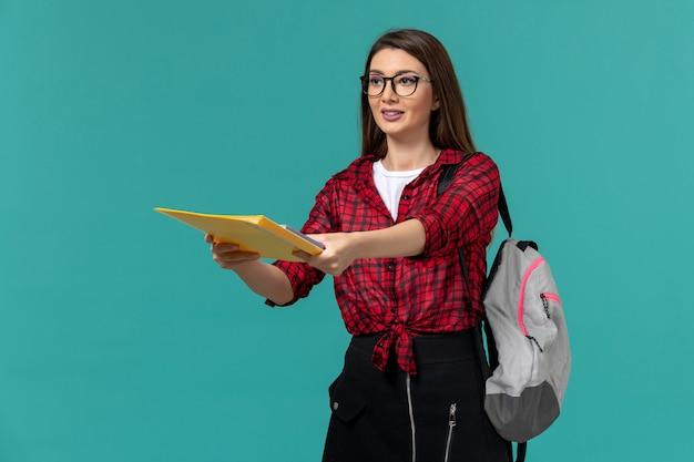 Vista frontal da aluna usando mochila e segurando arquivos na parede azul clara