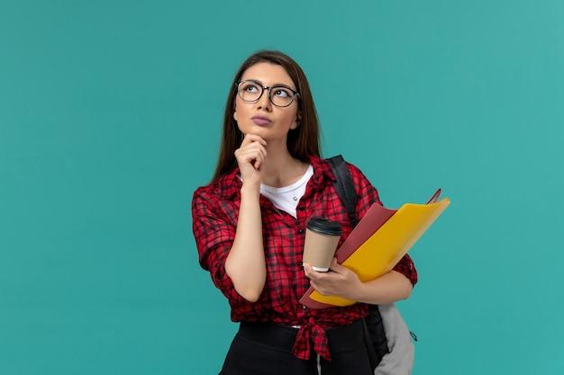Vista frontal da aluna usando mochila segurando arquivos e café pensando na parede azul-clara