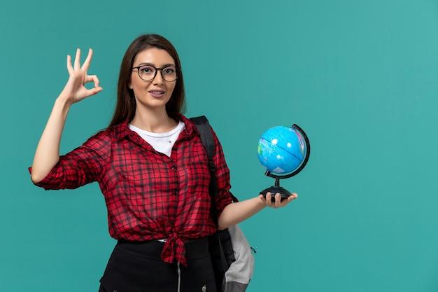 Vista frontal da aluna usando mochila segurando o globo na parede azul clara
