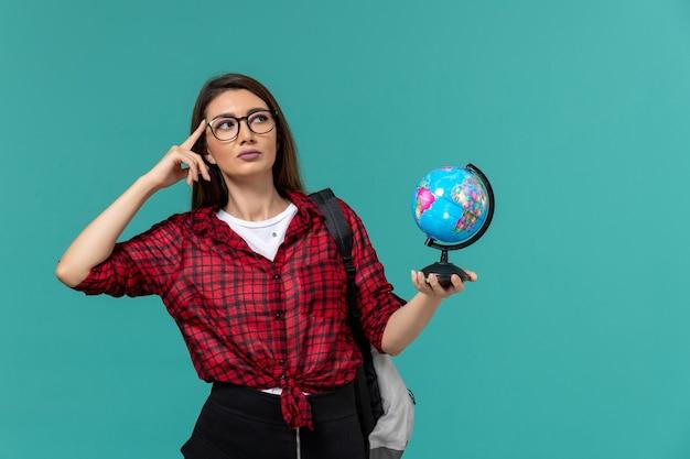 Vista frontal da aluna usando mochila segurando o pequeno globo pensando na parede azul clara