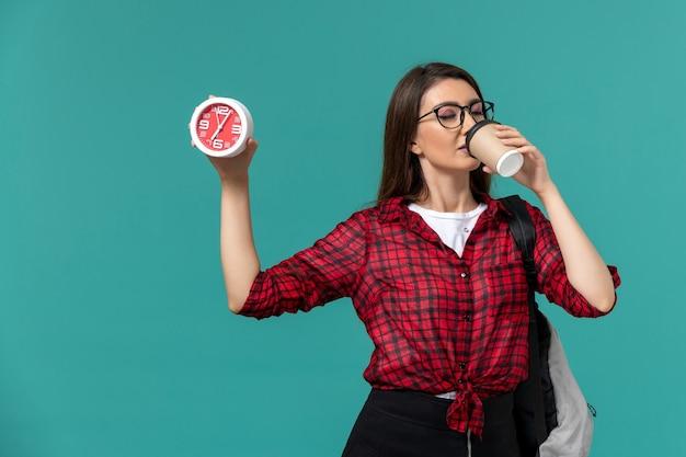 Vista frontal da aluna usando mochila segurando relógios e bebendo café na parede azul