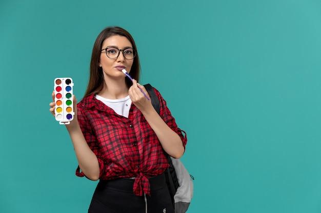 Vista frontal da aluna usando mochila segurando tintas e borlas na parede azul