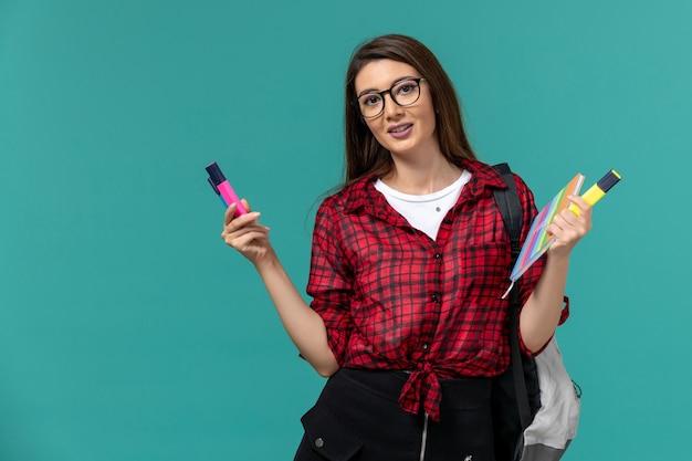 Vista frontal da aluna usando uma mochila segurando um caderno e canetas hidrográficas na parede azul