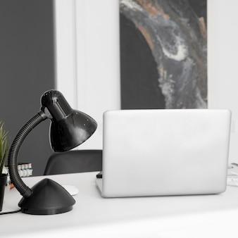 Vista frontal da área de trabalho do escritório com lâmpada e laptop