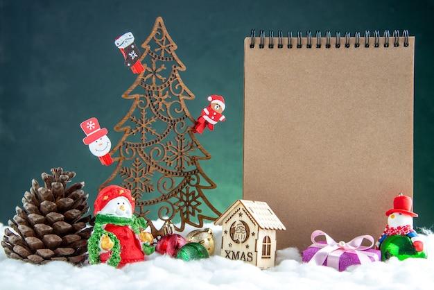 Vista frontal da árvore de natal de madeira com brinquedos pinha notebook pequena casa de madeira