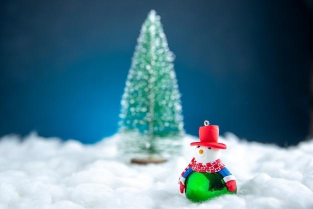 Vista frontal da árvore de natal do boneco de neve pequeno na superfície branca e azul