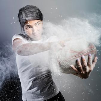 Vista frontal da atleta feminina de rúgbi segurando uma bola com pó