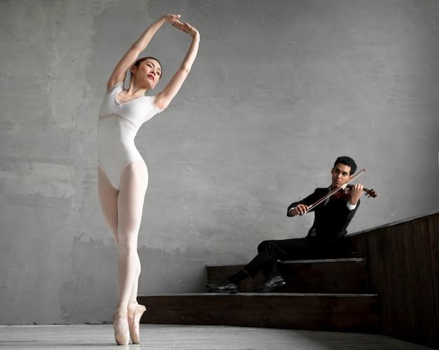 Vista frontal da bailarina dançando a música tocada pelo violinista masculino