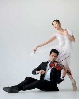 Vista frontal da bailarina e músico tocando violando