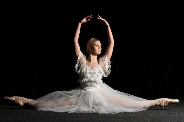 Vista frontal da bailarina posando ao fazer uma divisão