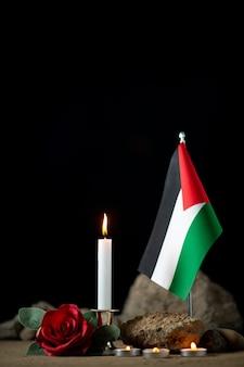 Vista frontal da bandeira palestina com velas acesas no escuro