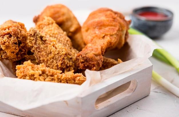 Vista frontal da bandeja de frango frito