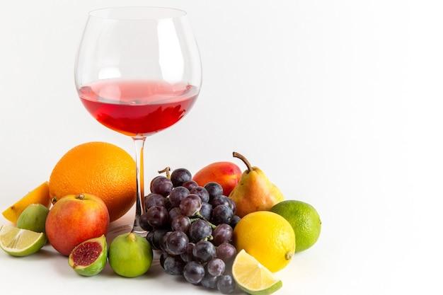 Vista frontal da bebida vermelha com álcool dentro de um copo com diferentes frutas frescas na parede branca.