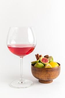 Vista frontal da bebida vermelha com álcool dentro de um copo com figos doces frescos na superfície branca