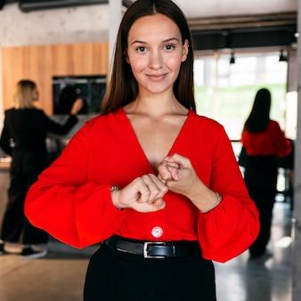 Vista frontal da bela empresária usando linguagem de sinais