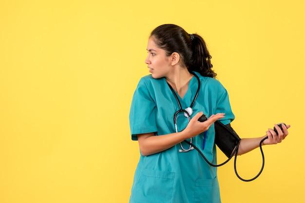 Vista frontal da bela médica de uniforme usando esfigmomanômetros em pé sobre fundo amarelo