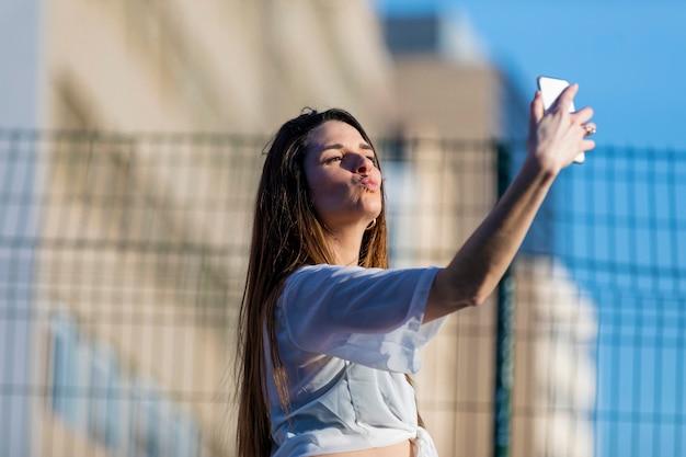 Vista frontal da bela moda jovem vestindo roupas casuais em pé na rua enquanto estiver a tomar uma selfie sorrindo em um dia ensolarado