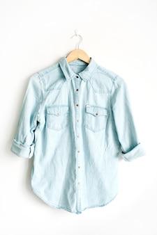 Vista frontal da beleza da t-shirt jeans azul da moda em cabide perto de fundo branco. conceito de moda.