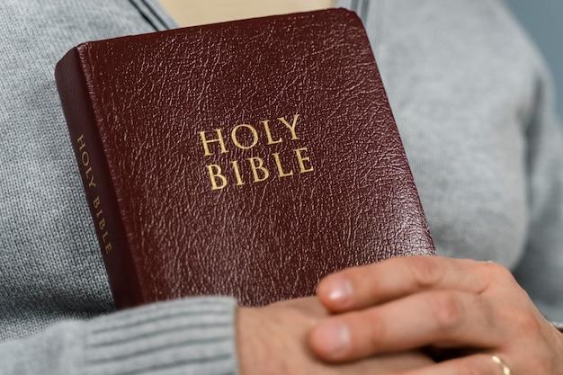 Vista frontal da bíblia sagrada nos braços do homem