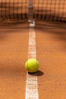 Vista frontal da bola de tênis no campo do tribunal