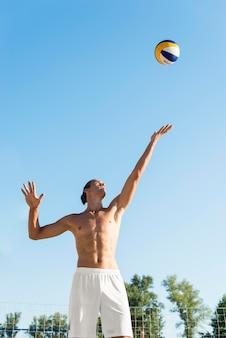 Vista frontal da bola sacando jogador masculino sem camisa de voleibol