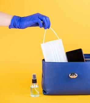 Vista frontal da bolsa com máscara médica e desinfetante para as mãos