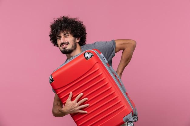 Vista frontal da bolsa de transporte masculino jovem e se preparando para uma viagem no espaço rosa