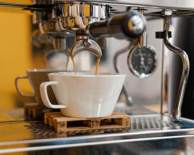 Vista frontal da cafeteira com xícara