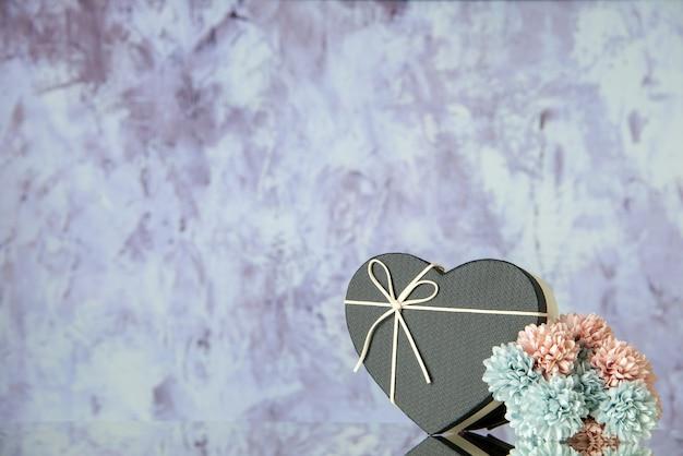 Vista frontal da caixa de coração com flores coloridas de capa preta em fundo cinza abstrato com espaço livre