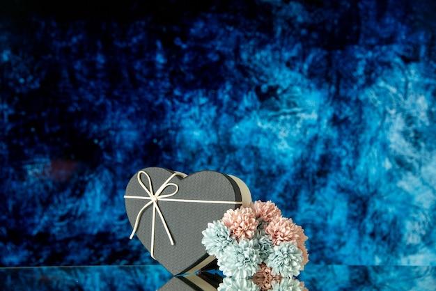 Vista frontal da caixa de coração preto com flores coloridas em fundo abstrato azul escuro