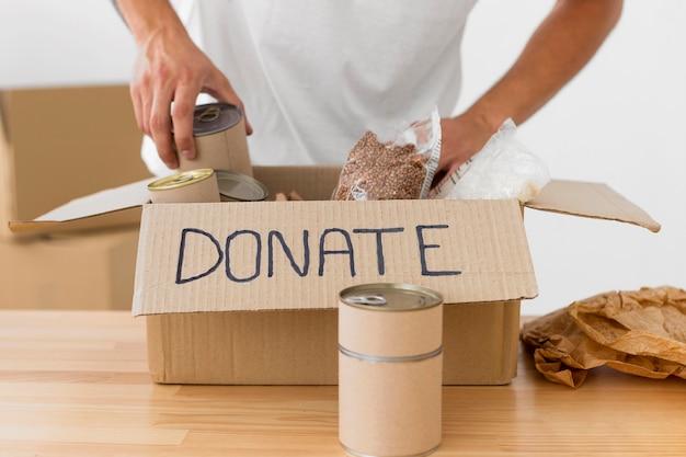 Vista frontal da caixa de doações em mesa de madeira