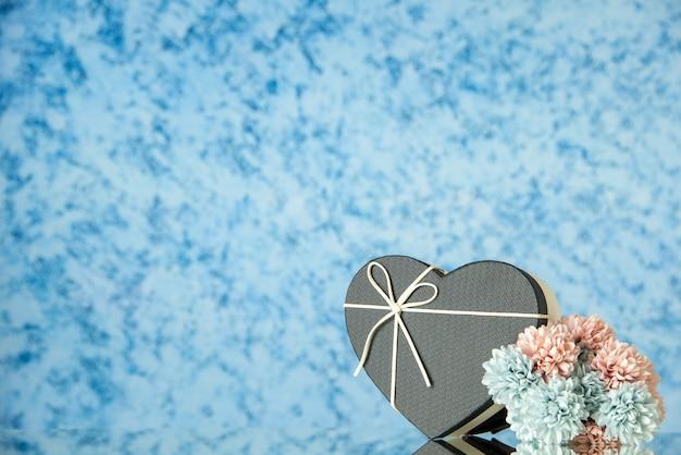 Vista frontal da caixa de flores em forma de coração preto em azul desfocado