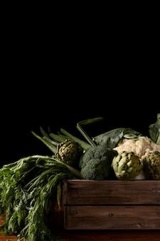 Vista frontal da caixa de madeira com vegetais verdes