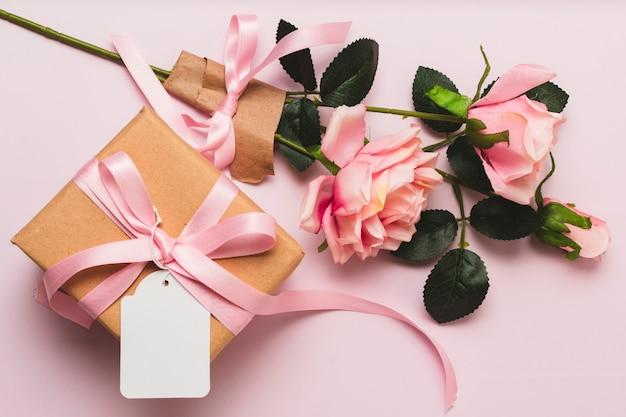 Vista frontal da caixa de presente com buquê de rosas e fita