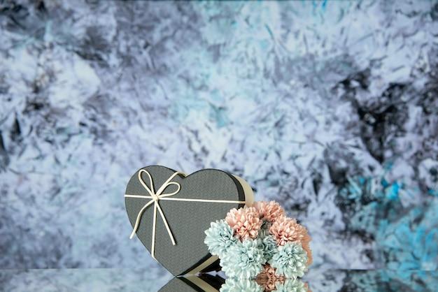 Vista frontal da caixa do coração preto com flores coloridas no espaço livre do fundo abstrato cinza