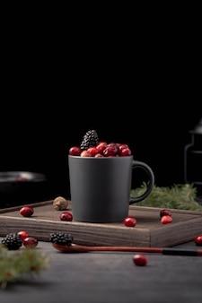 Vista frontal da caneca com cranberries e amoras
