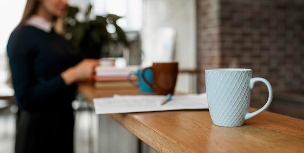 Vista frontal da caneca de café no balcão da mesa com a mulher desfocada