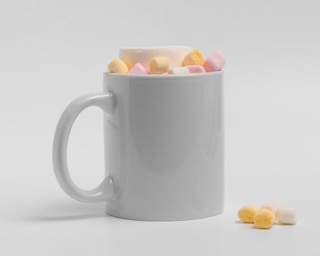 Vista frontal da caneca de natal com bebida e marshmallows
