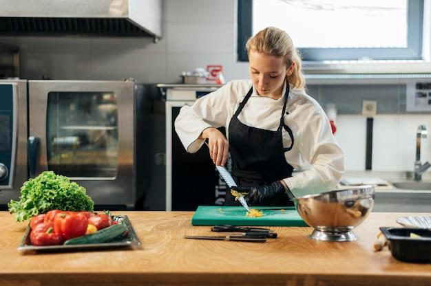 Vista frontal da chef feminina na cozinha fatiando legumes