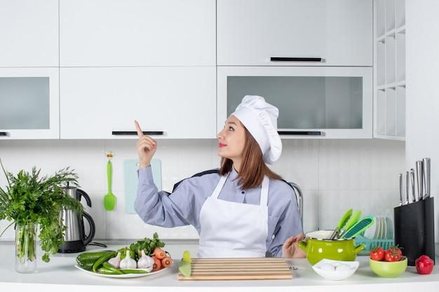 Vista frontal da chef feminina sorridente e positiva e legumes frescos apontando para cima no lado direito na cozinha branca
